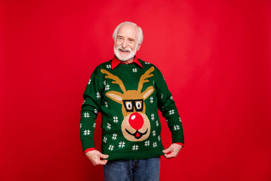 persona mayor enseñanso su pareja con el mismo jersey navideño